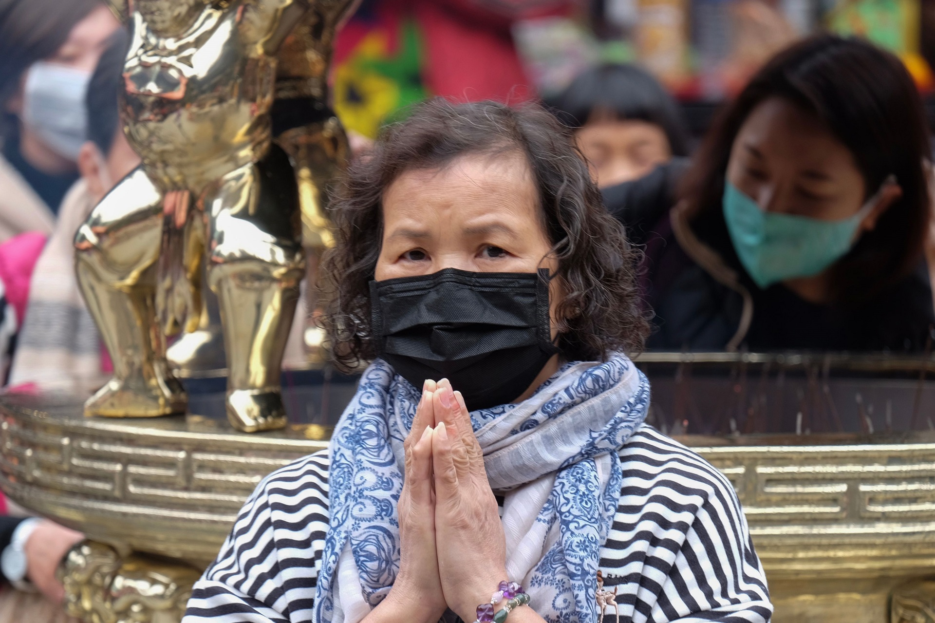 coronavirus spreading in Asia old woman praying at temple in facemask